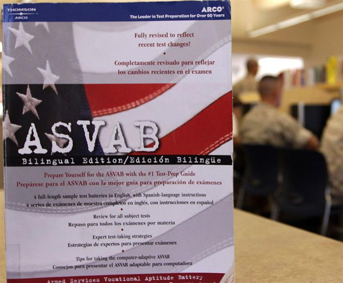asvab booklet on table and students taking test in background