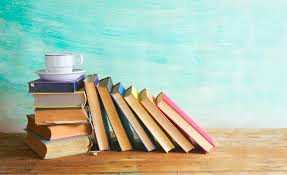 A stack of books with a coffee cup on top of them.